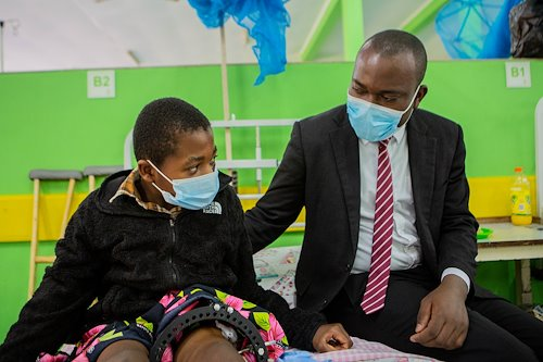 The Spiritual Director spends his time in the ward. Chimwemwe, the Spiritual director , has a chat with a child by his bedside.