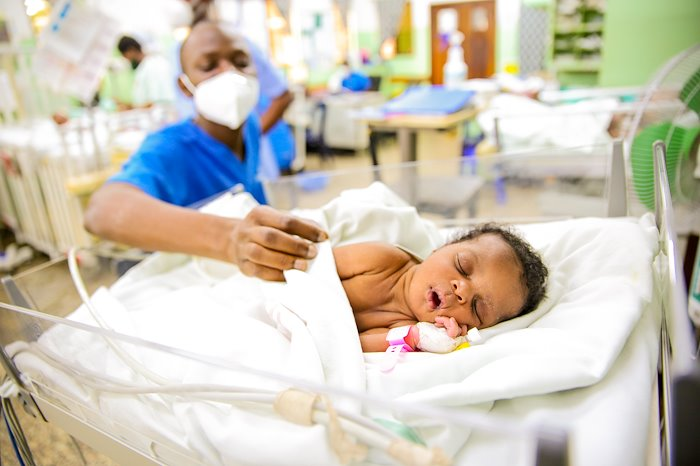 A baby sound asleep in the ward as our nurse closely monitors.