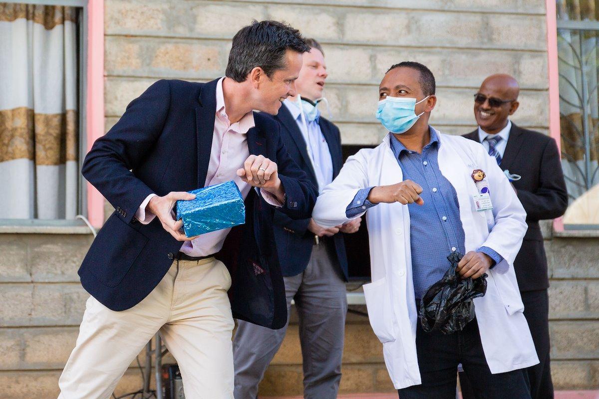 Dr. Rick elbow bumps Dr. Mesfin after an appreciation speech.