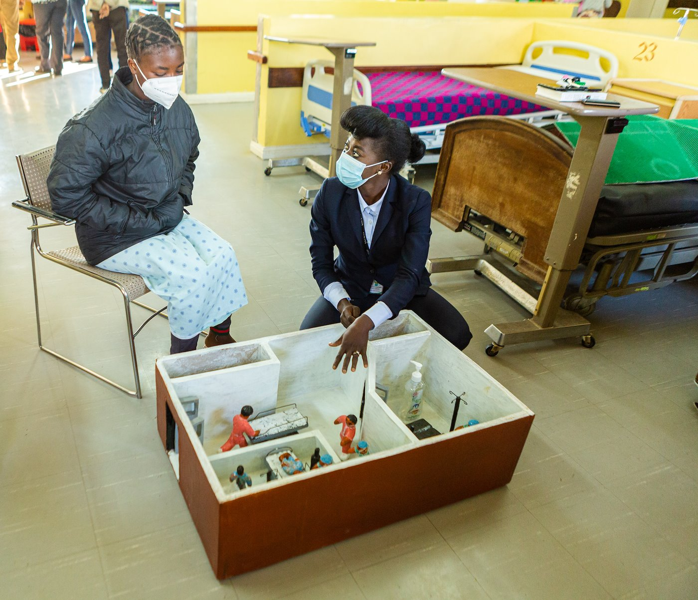 Lillian prepping a child going for surgery with the aid of a Surgery house.