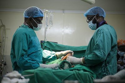 Dr. Sough and Dr. Muka praying for a patient before surgery.