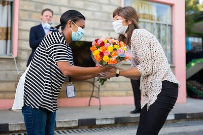 Dr. Rick's wife Anne receives flowers from Nurse Matron Sara.