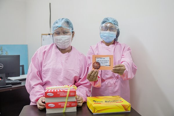 Social Workers Mona and Gina are happy to receive sweets from a grateful patient who received treatment at CURE Philippines.